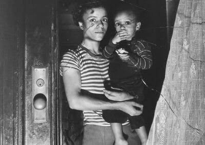 "Weegee, Mrs. Bernice Lythcott and her one-year-old son Leonard look out a window through which hoodlums threw stones., October 18, 1943, Silver gelatin print, printed in 1981 by Sid Kaplan 16 x 12 in., From the ""Weegee Collection"" portfolio printed in 1980. Only three complete sets printed out of the edition of twenty, plus various additional prints of certain images. Full negative, ""Weegee Collection"" embossed blindstamp in border corner. Weegee collection embossed blind stamp in lower right border on recto. Notated ""6/3"" in lower left quadrant in pencil on verso."