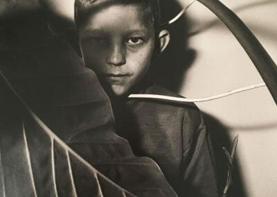 """Roger Ballen, Untitled, Boy with leaf, 1999, Vintage selenium toned gelatin silver print, 14 x 14 in., Photographer's signature, title, and date in pencil, annotated """"shot-1999 printed- 1999 Edition 9/35 Paper Ilford Gallery Selenium toned"""", """"Good Toned Spotted (2)"""", """"7314-RBA"""", and """"P30017"""" in pencil on verso."""