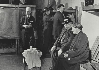 "Robert Capa, London, England, evening tea in an air raid shelter, June-July 1941, Vintage silver gelatin print, 6 x 5 11/16 in., Magnum Stamp with description and illustration information, copyright Robert Capa/ Magnum photos stamp, annotated ""P.201.5.30"" in pencil on verso."