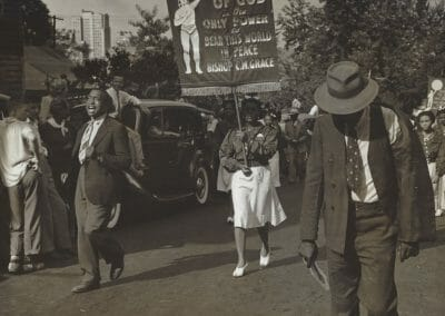 """Rosalie Gwathmey, Parade, Charlotte, N.C., 1947, Vintage silver gelatin print, 7 5/16 x 9 7/16 in., Photographer's signature in pencil, label adhered stating """"Charlotte, N.C. Every September first there is a parade for Bishop Grace. He is the Father Divine of the South"""", New York Public Library stamp, New York Public Library - Picture Collection stamp with notations in pencil, Photographer's N.Y.C. stamp, annotated """"RG91"""" in pencil on verso."""